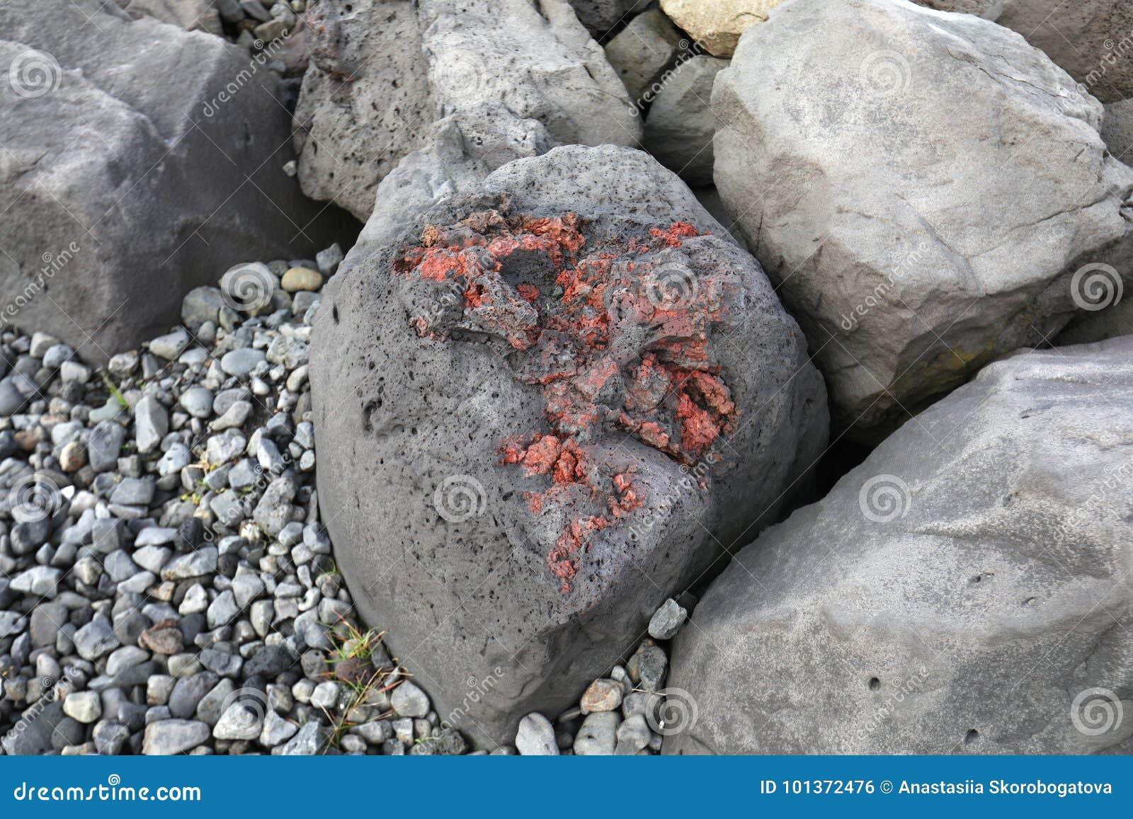 Rote vulkanische Steine in dem Ozean