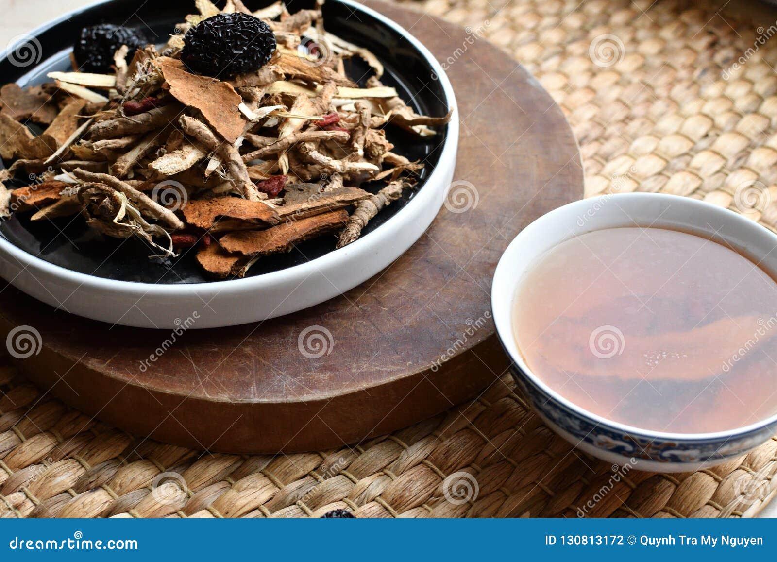 Roteiro chinês da medicina tradicional Tisana com jujuba, bagas do goji, raizes do gingseng e outro no papel de pergaminho no neu