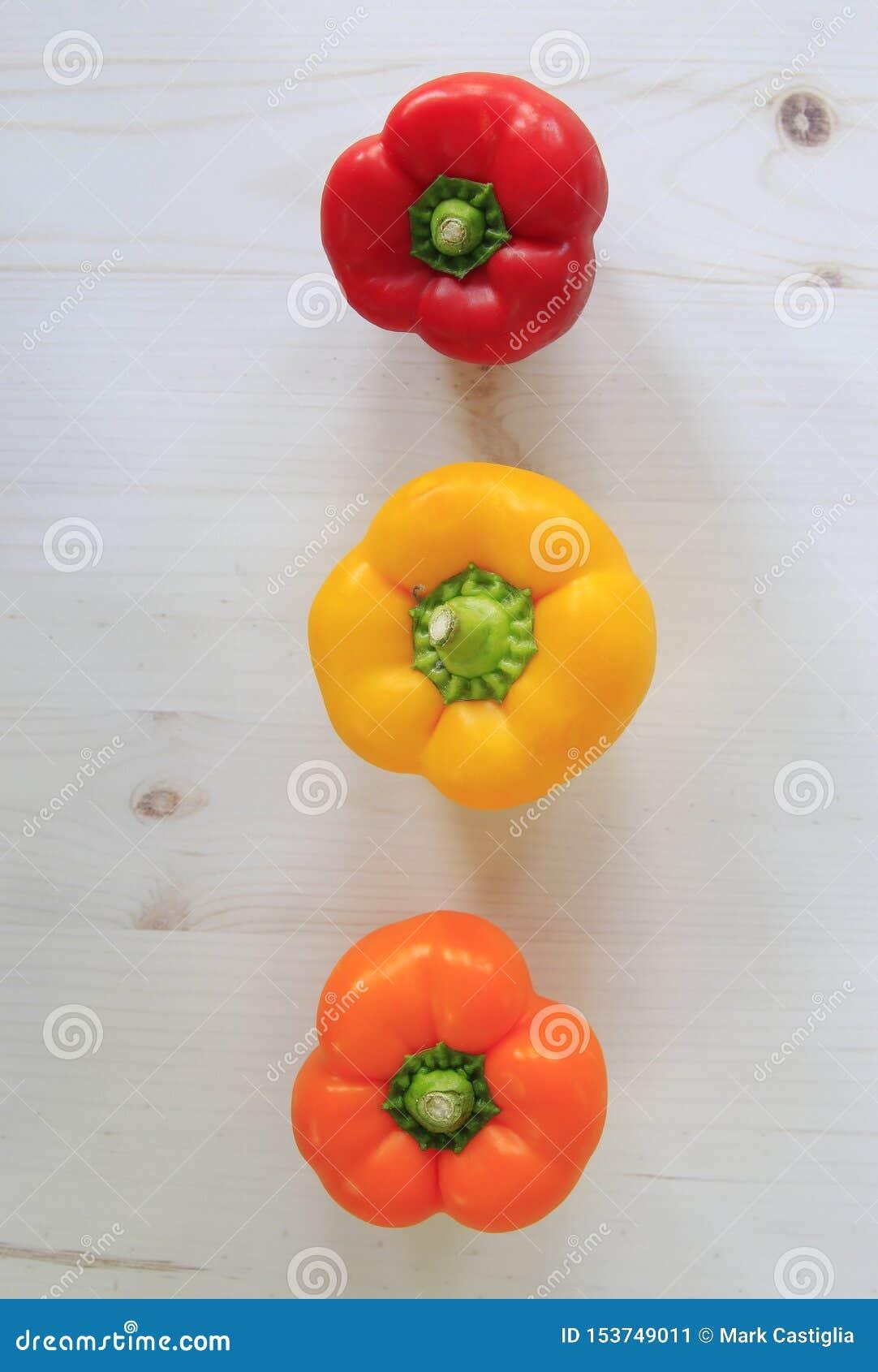 Roter, gelber und orange grüner Pfeffer ausgerichtet auf Plankenhintergrund Flache Lage