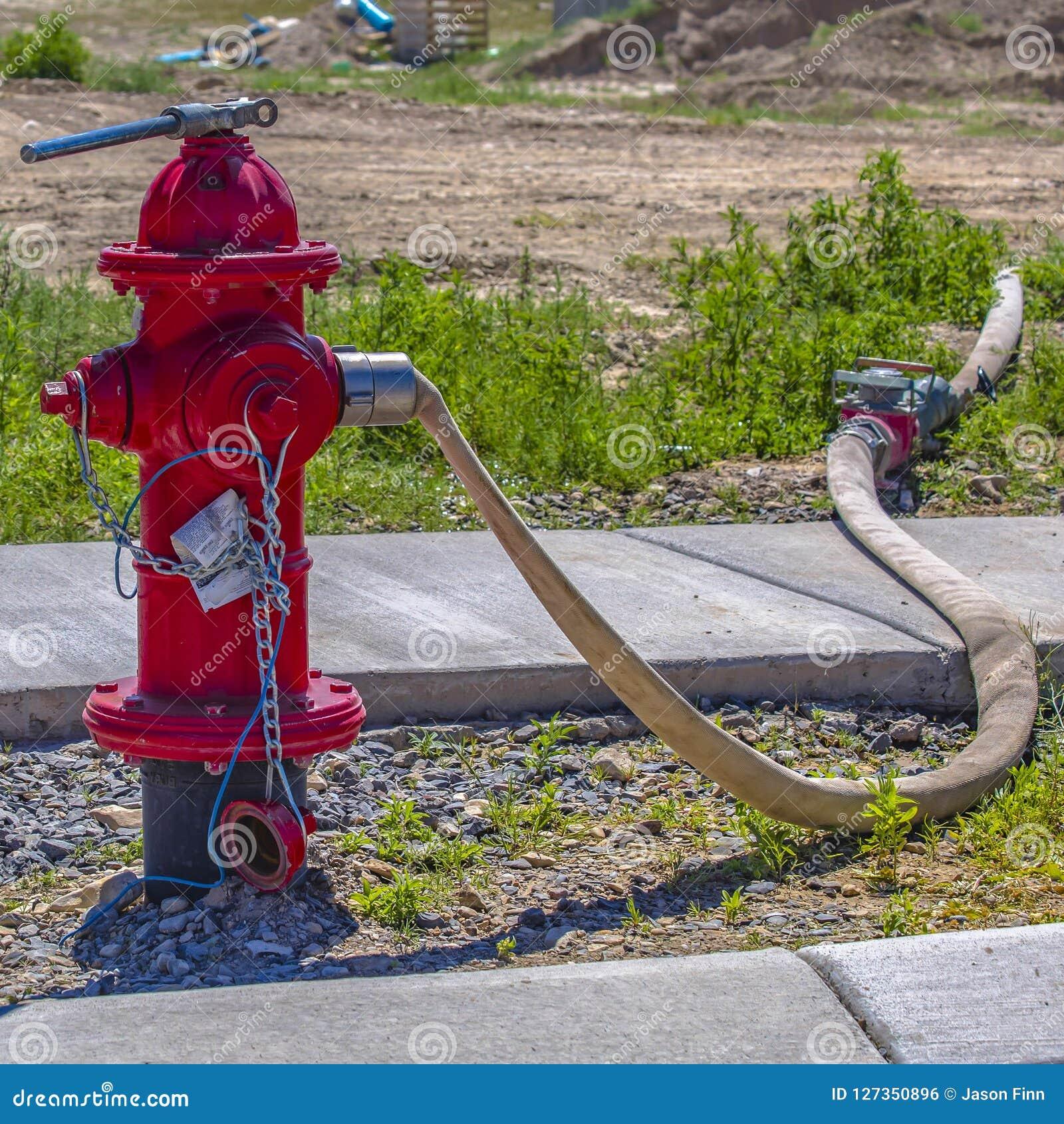 Roter Hydrant mit dem Schlauch angeschlossen an Ausgang