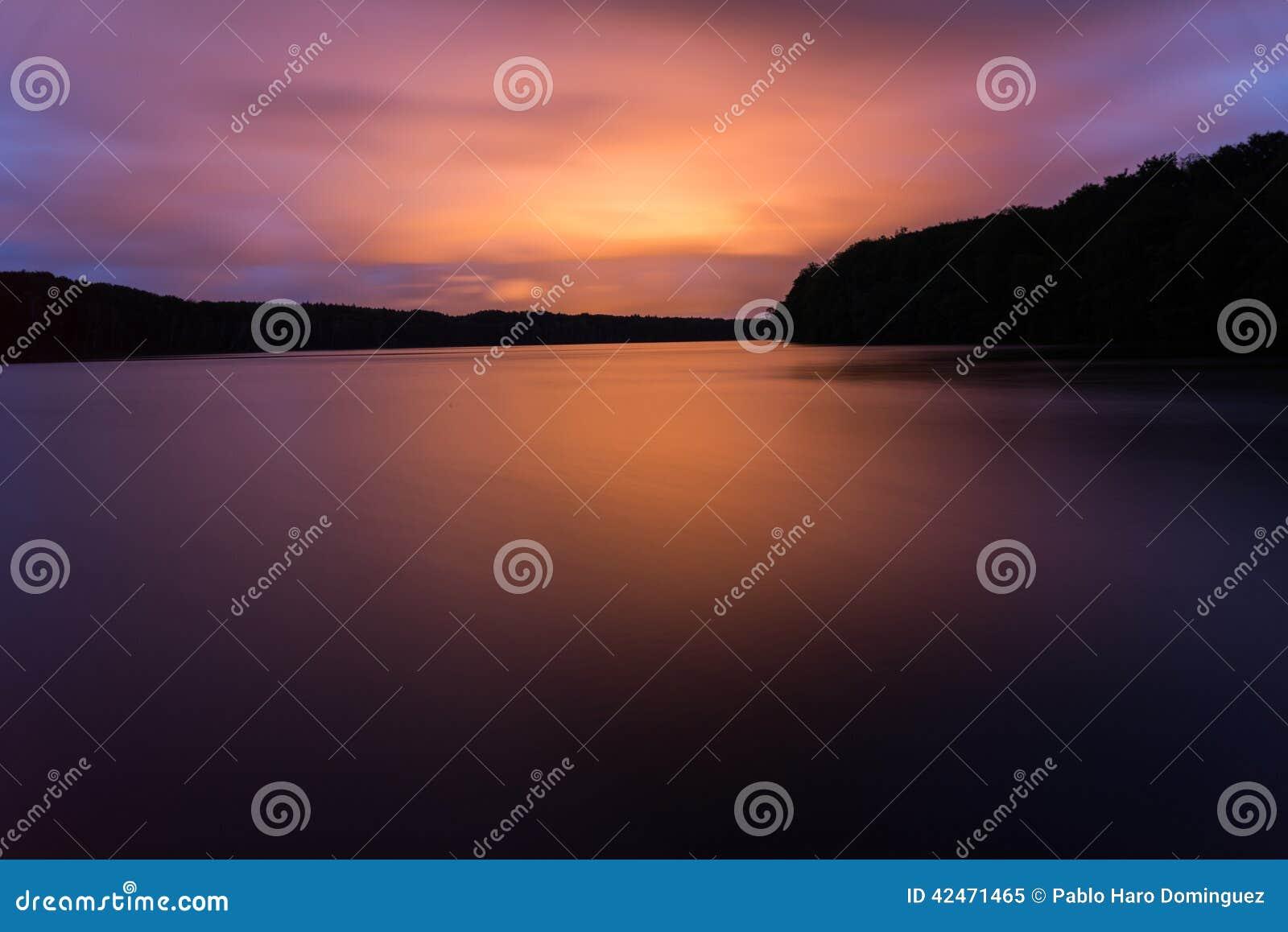 Roter Lichtreflex auf einem See in einem großartigen Sonnenuntergang