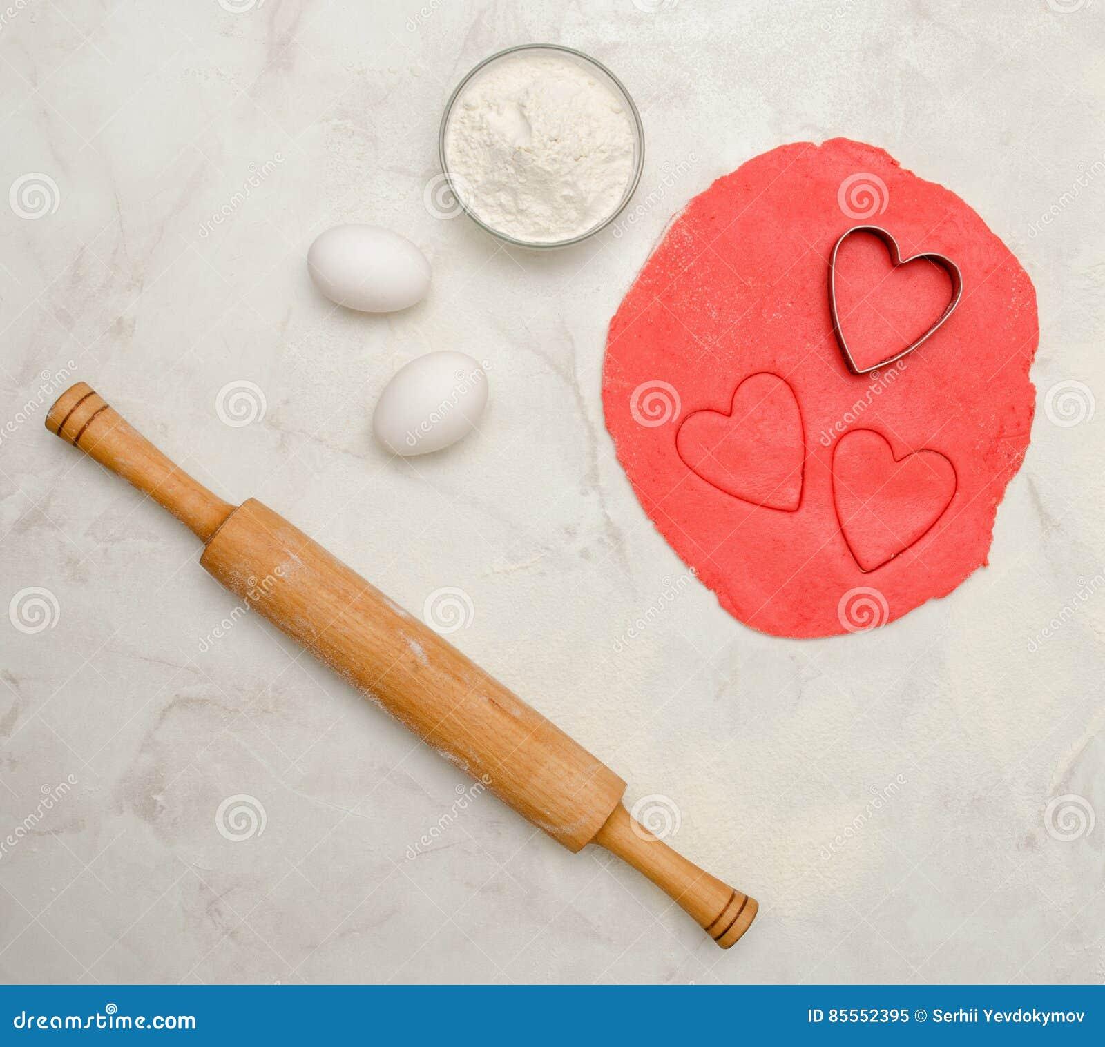 Roter Teig mit einem herausgeschnittenen Herzen, Eiern, Mehl und Nudelholz, auf einer weißen Tabelle Draufsicht, Raum für Text