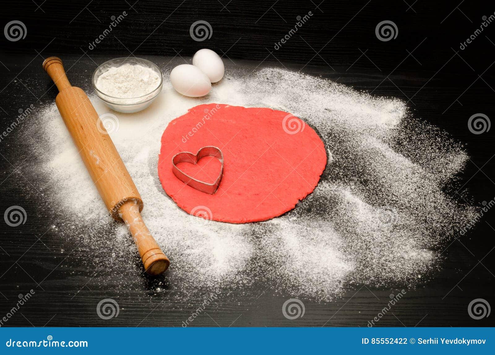 Roter Teig, zum von von Ausschnittherzen und -mehl auf der schwarzen Tabelle, ein Nudelholz zu bilden Beschneidungspfad eingeschl