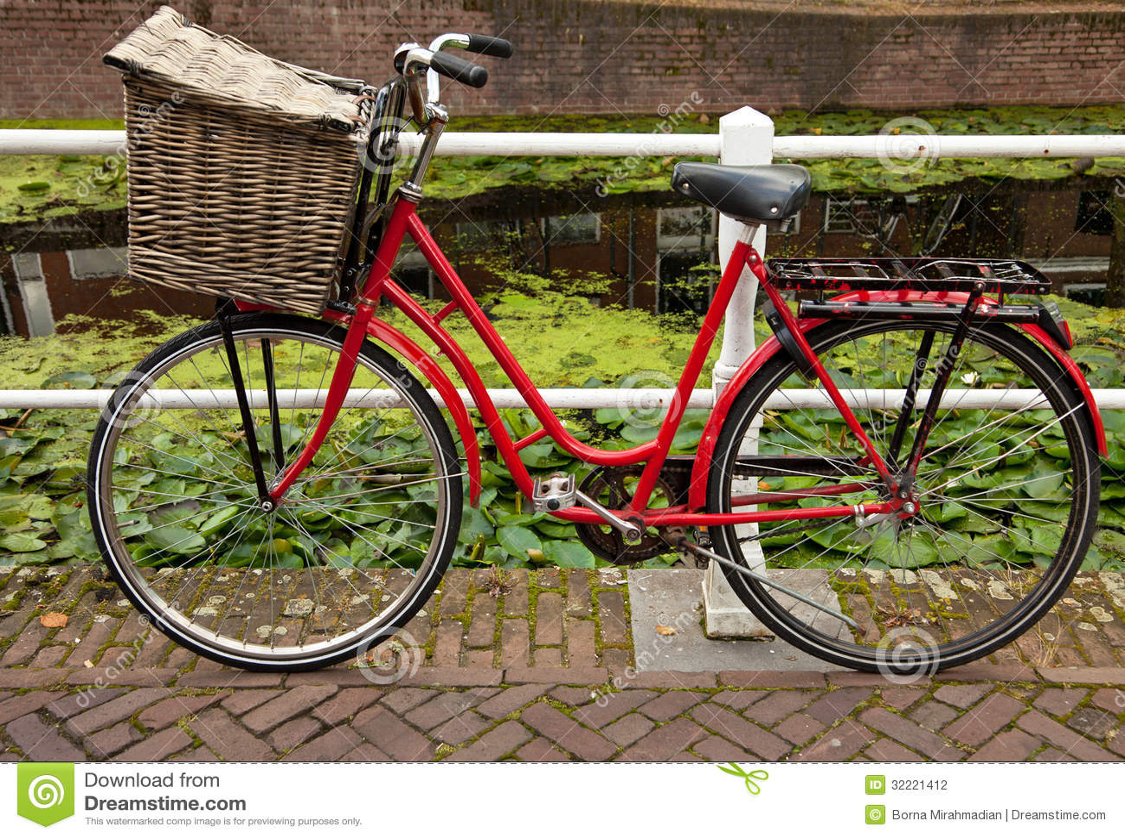 rotes fahrrad mit dem korb geparkt neben kanal in holland. Black Bedroom Furniture Sets. Home Design Ideas