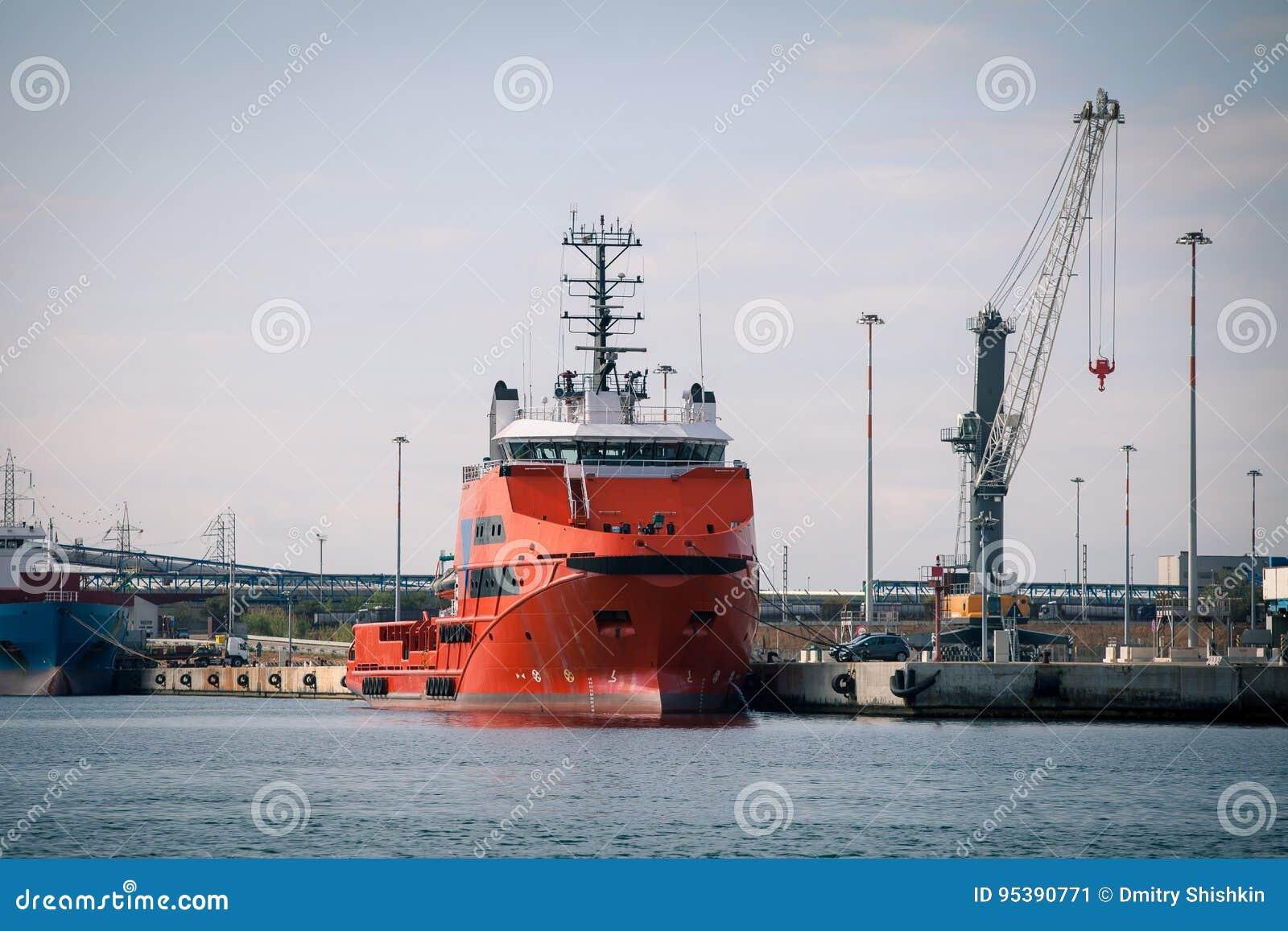 Rotes Frachtschiff vor Hafenanlagen und -kränen