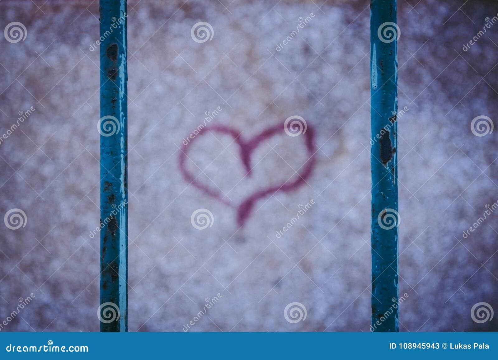 Rotes Graffitiherz Verrostender Zaun