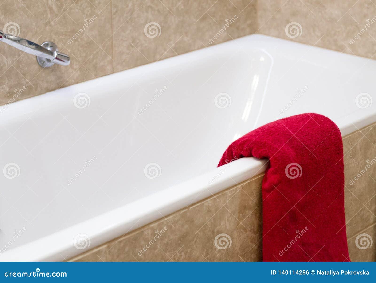 Rotes Terry-Badtuch ist auf Bad mit beige Fliesen