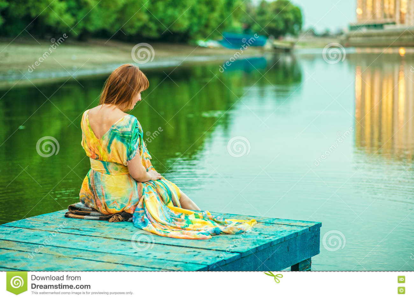 Rothaarige Frau im hellen Sommerkleid mit dem offenen Rücken, der auf dem hölzernen Pier in der Flussbank sitzt