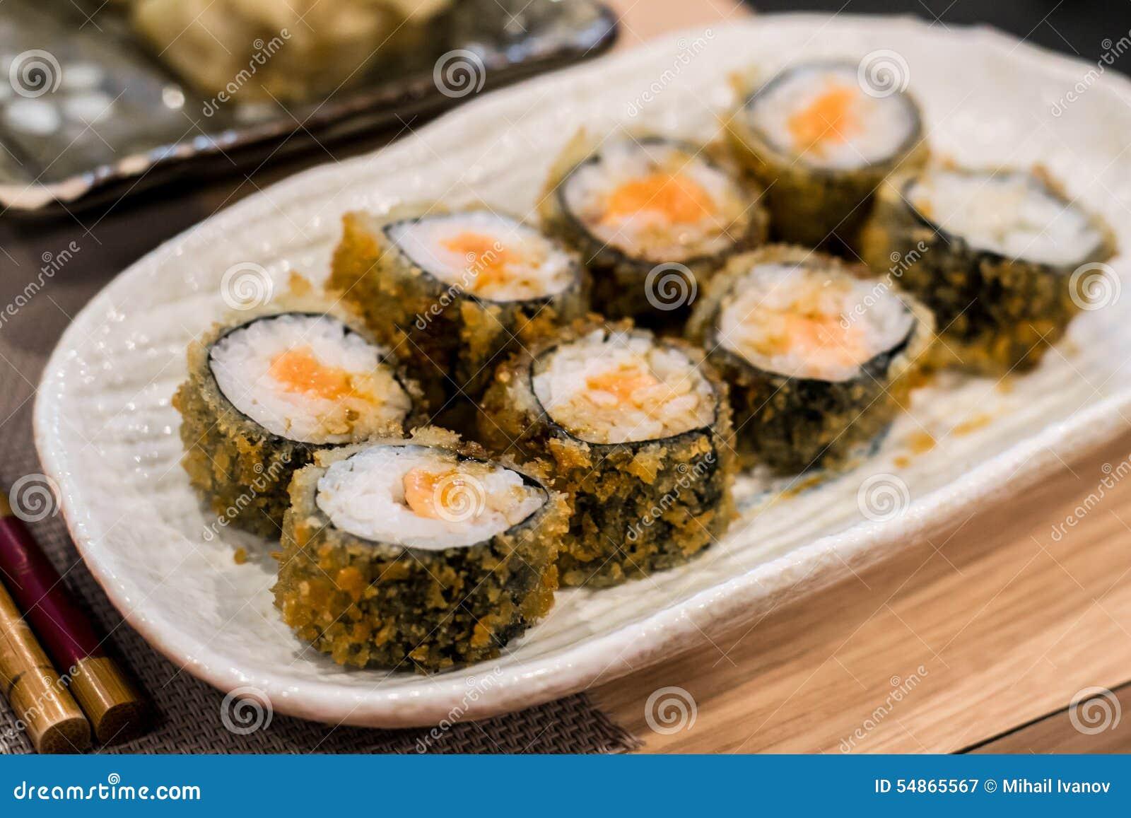 Rotoli di sushi fritti di hossomaki con il salmone crudo fresco ed il riso  bianco