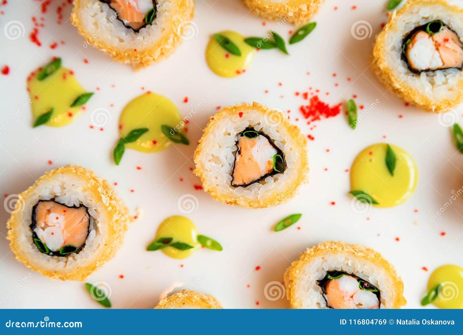 Rotoli di sushi sparsi su fondo bianco