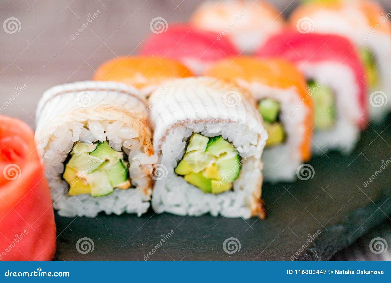 Rotolo di sushi dell arcobaleno sul vassoio con la fine dello zenzero su