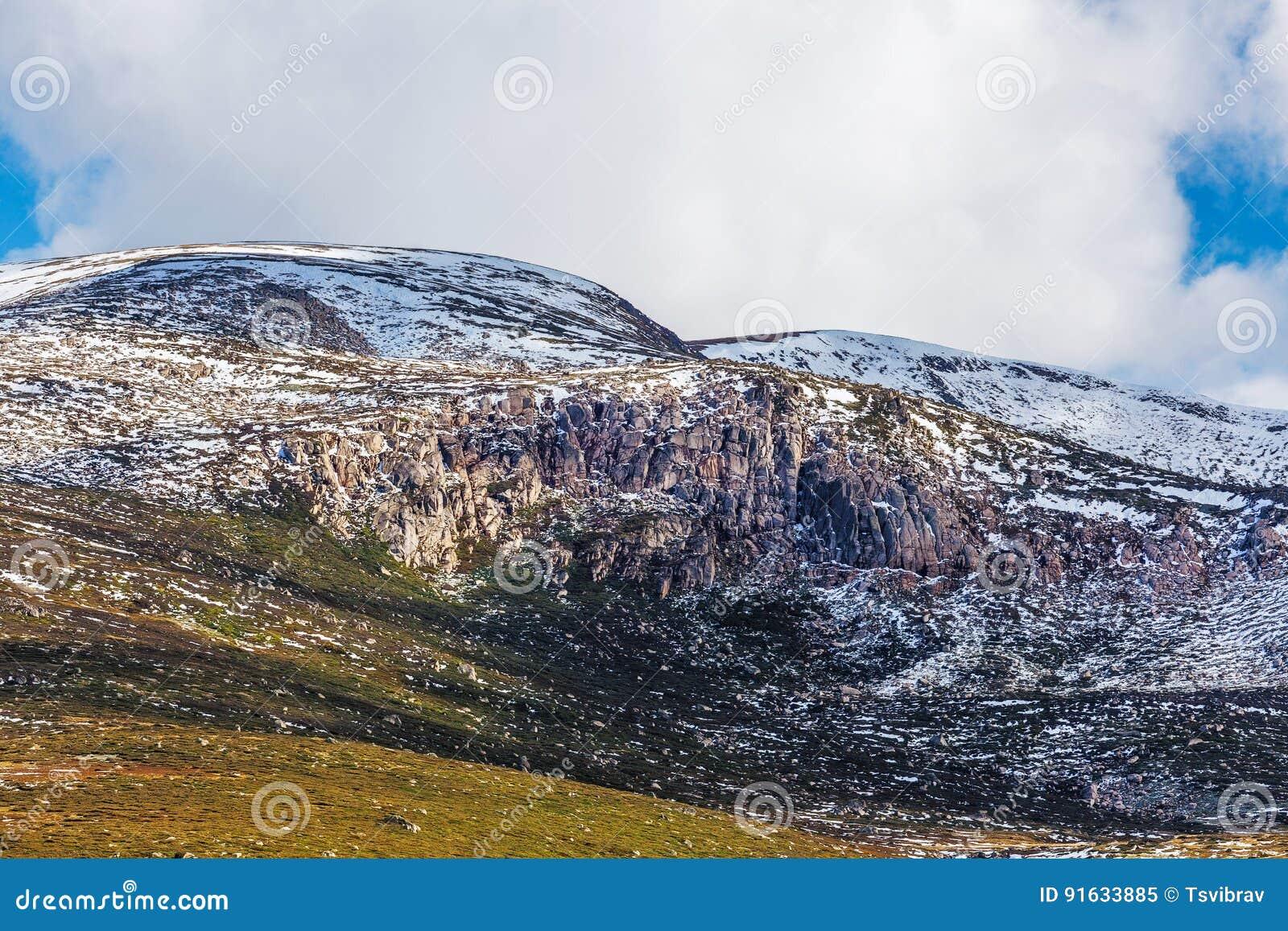 Rotsachtige dagzomende aardlagen die in sneeuw bij het Nationale Park van Onderstelkosciuszko worden behandeld
