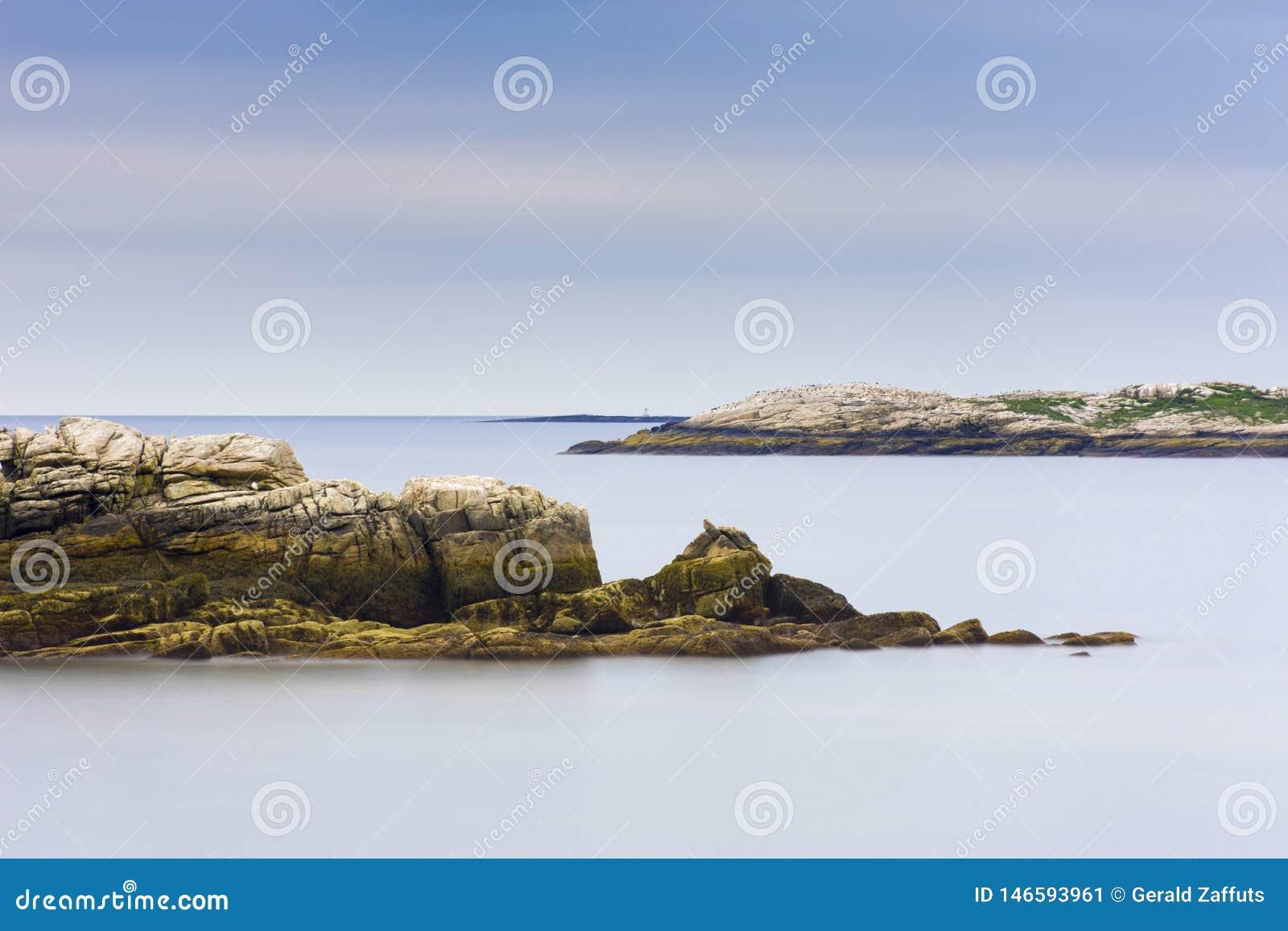 Rotsachtige de kustlijn van Maine met vlotte oceaan en blauwe hemel