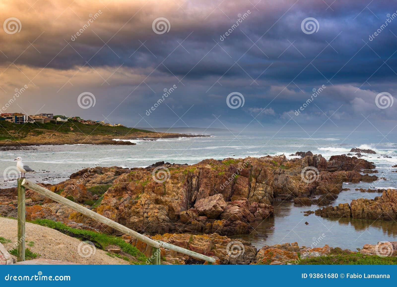 Rotsachtige kustlijn op de oceaan in DE Kelders, Zuid-Afrika, beroemd voor walvis het letten op Wintertijd, bewolkte en dramatisc