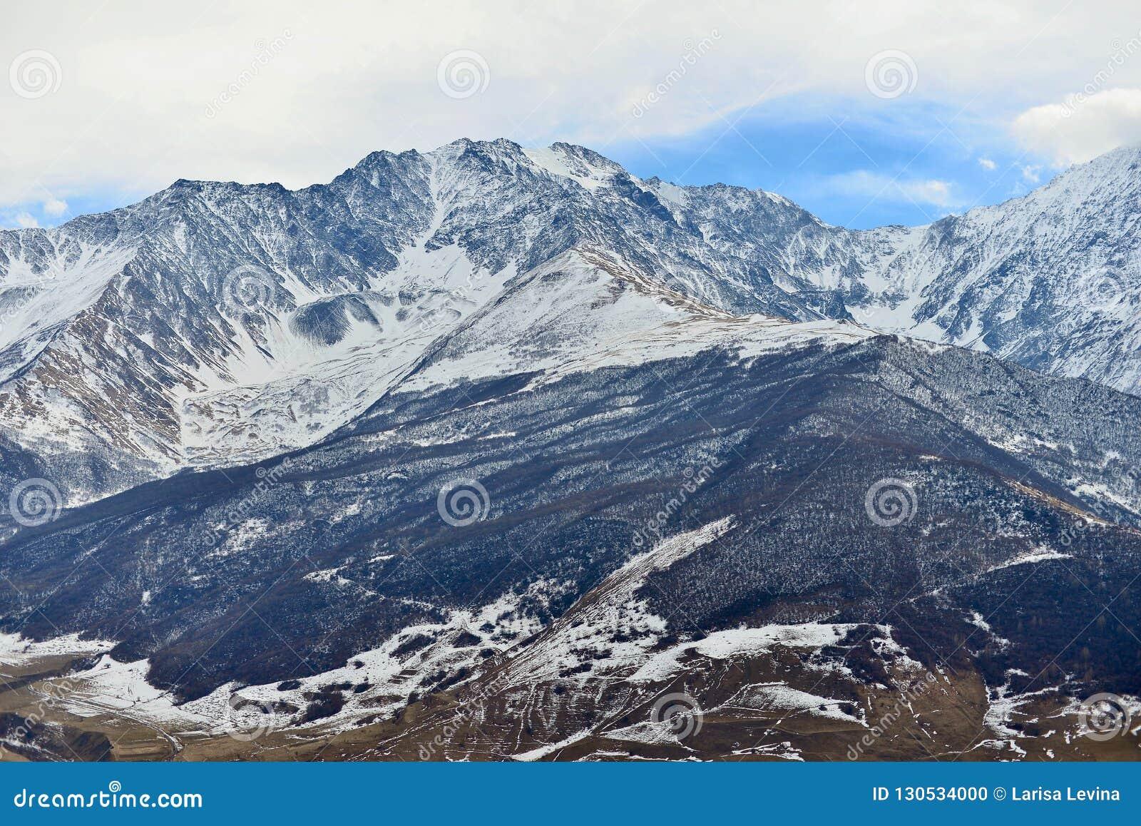 Rotsachtige snow-capped bergen over het dorp van Fiagdon