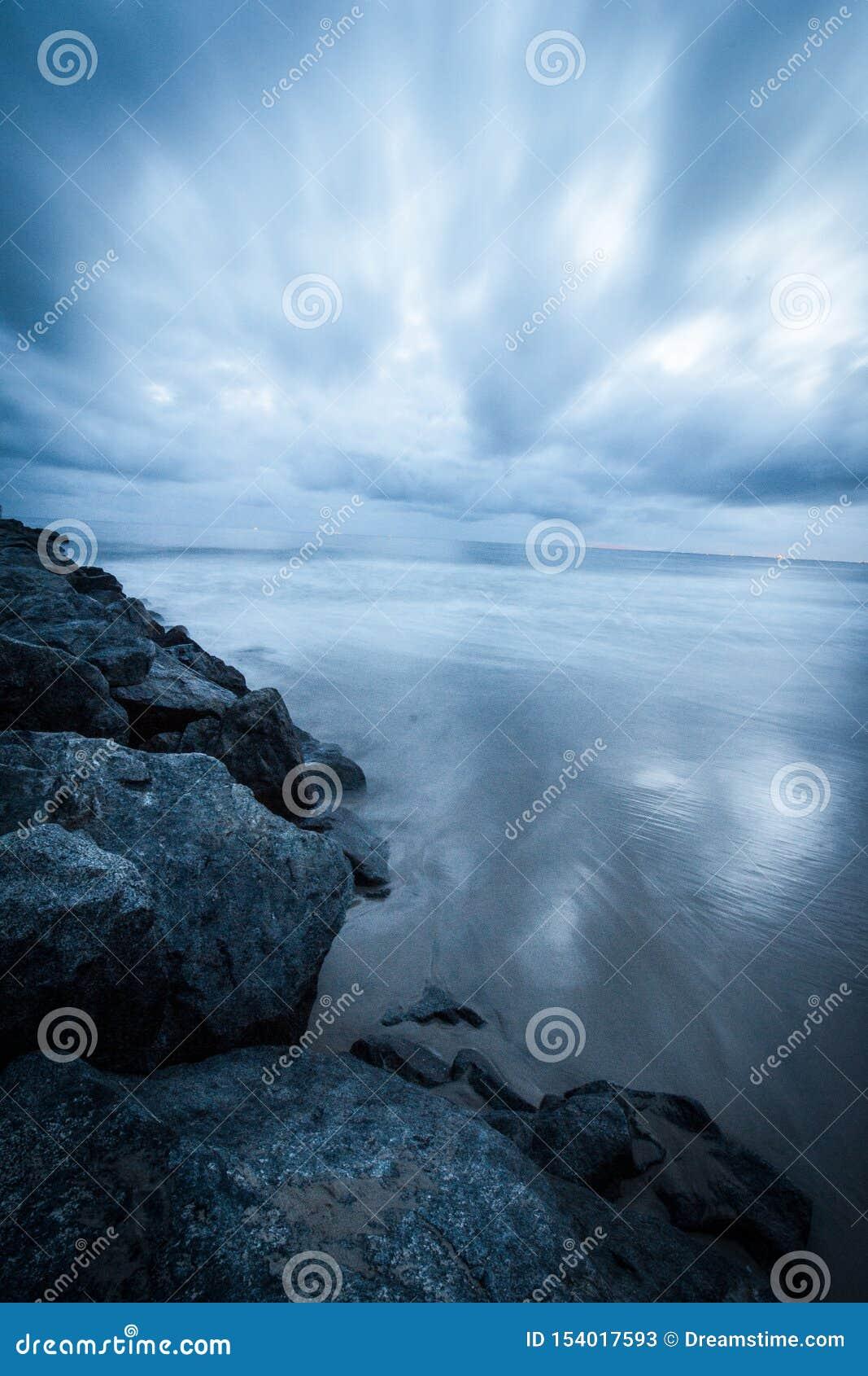Rotsen op de oceaan van de strandzonsondergang