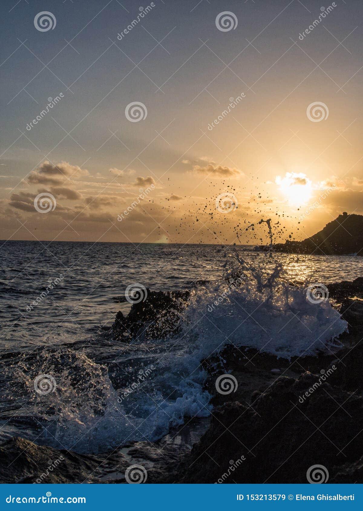 Roturas de la onda de la salida del sol en la roca, Pantelleria, Italia
