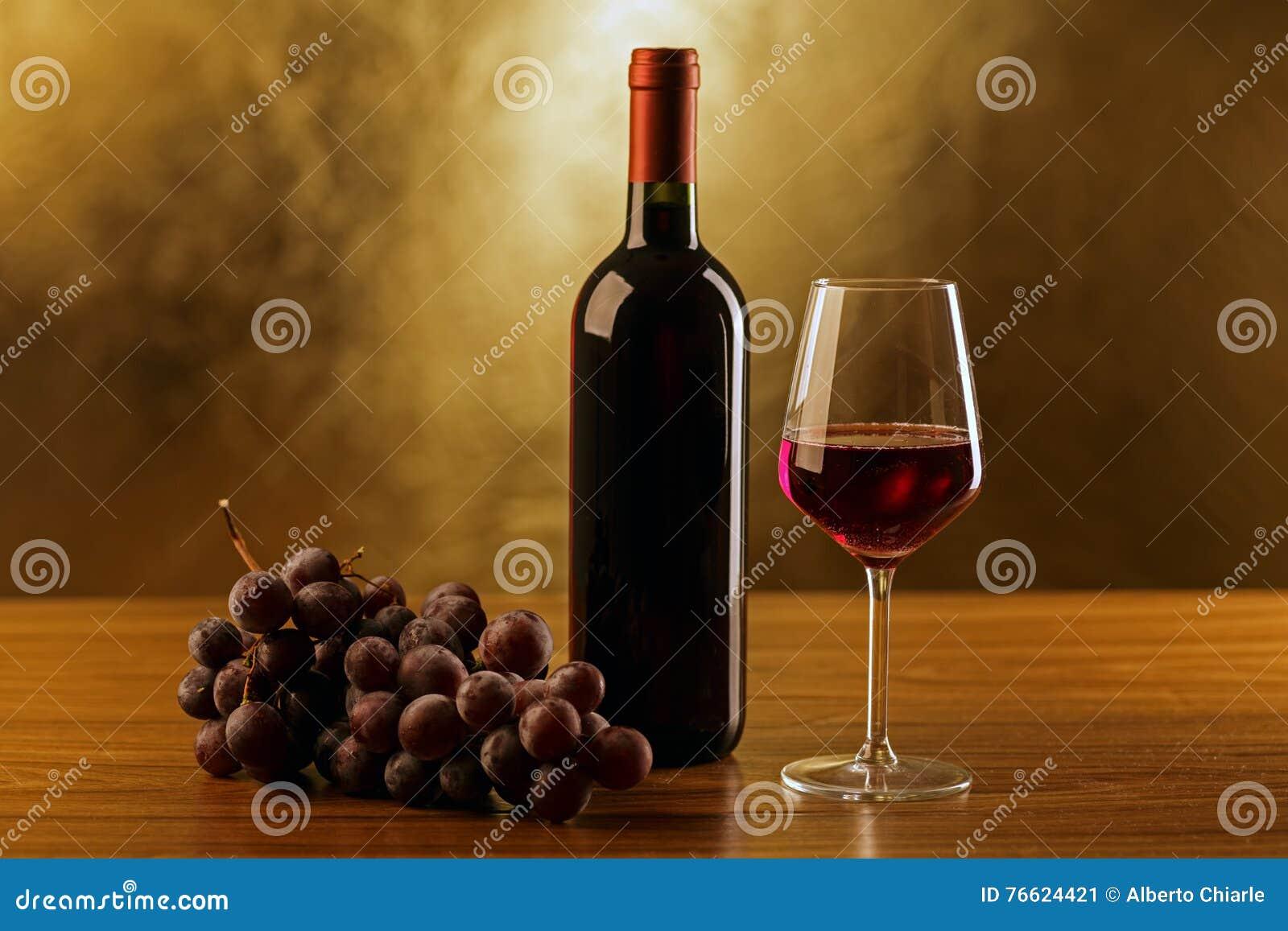 rotweinflaschen mit glas und trauben auf holztisch und. Black Bedroom Furniture Sets. Home Design Ideas