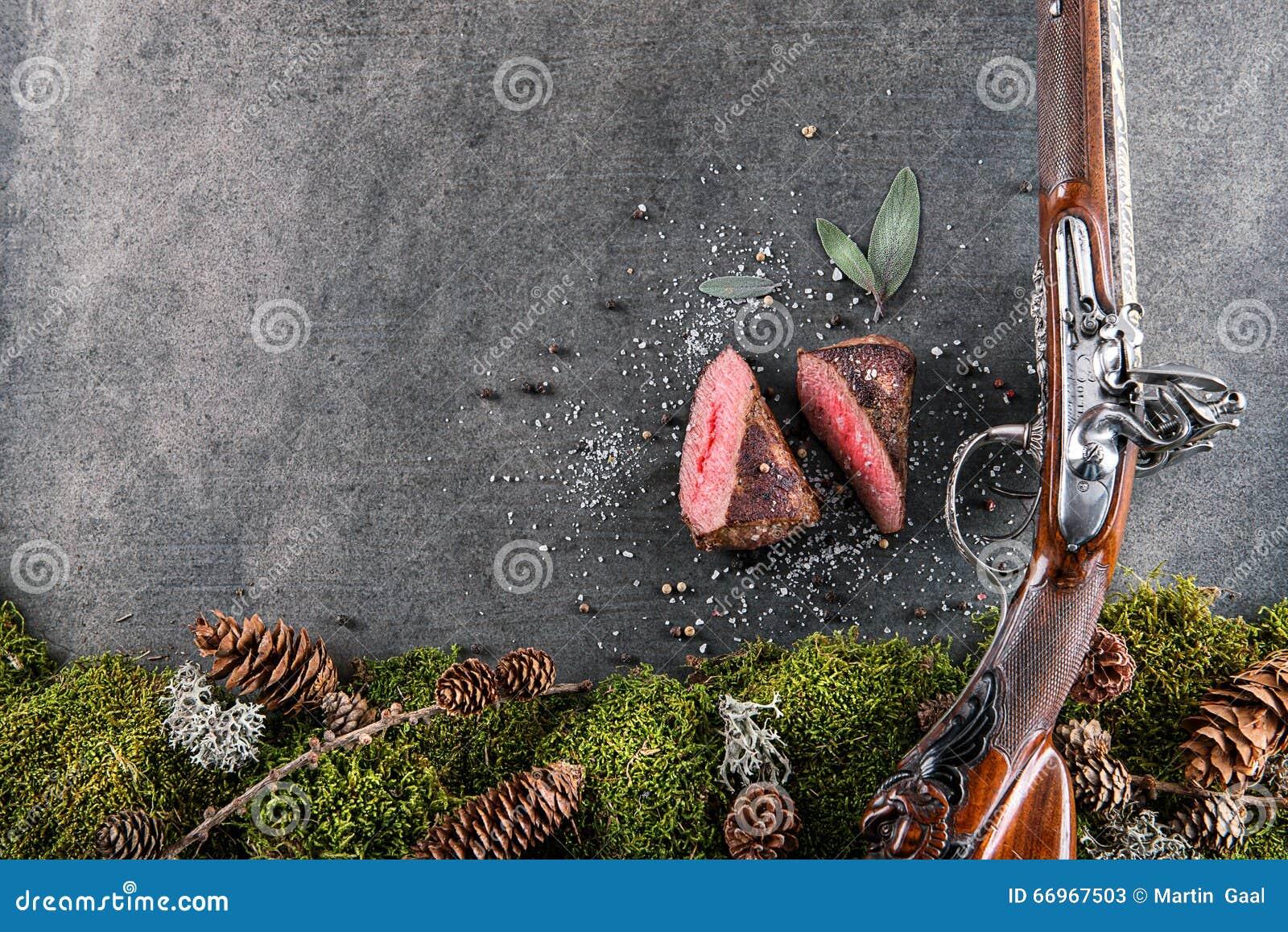 Rotwild- oder Wildbretsteak mit antikem Gewehr und Bestandteile mögen Seesalz, Kräuter und Pfeffer, Lebensmittelhintergrund für R