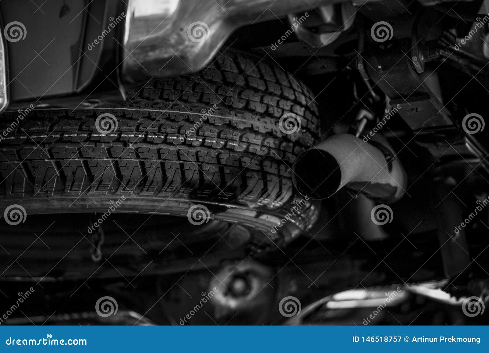 Roue de secours sous la voiture pr?s du pot d ?chappement Roue de secours Produit en caoutchouc Contrôle d automobile avant conce