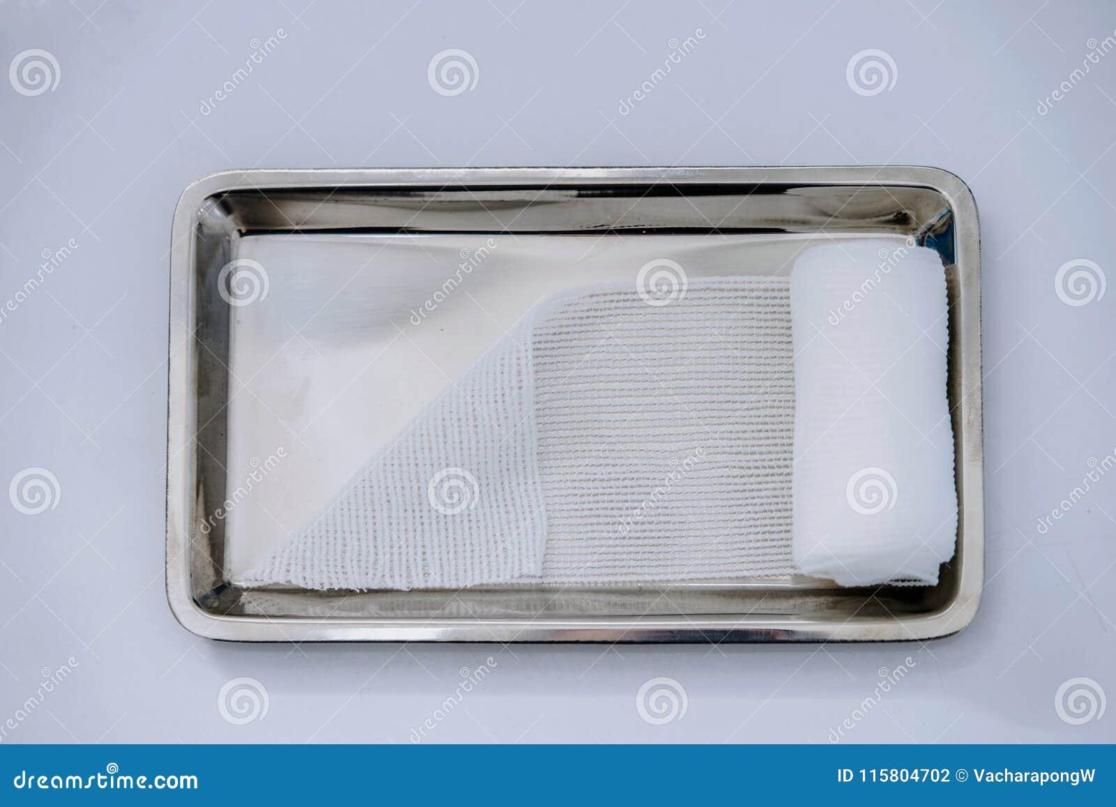 Roulez la gaze ou le bandage mince sur le plateau médical sur le CCB blanc
