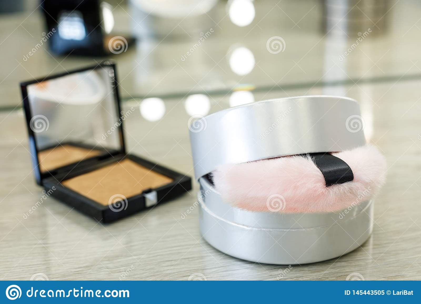 Round box with powder and pink fur sponge and rouge in a square box in a beauty salon