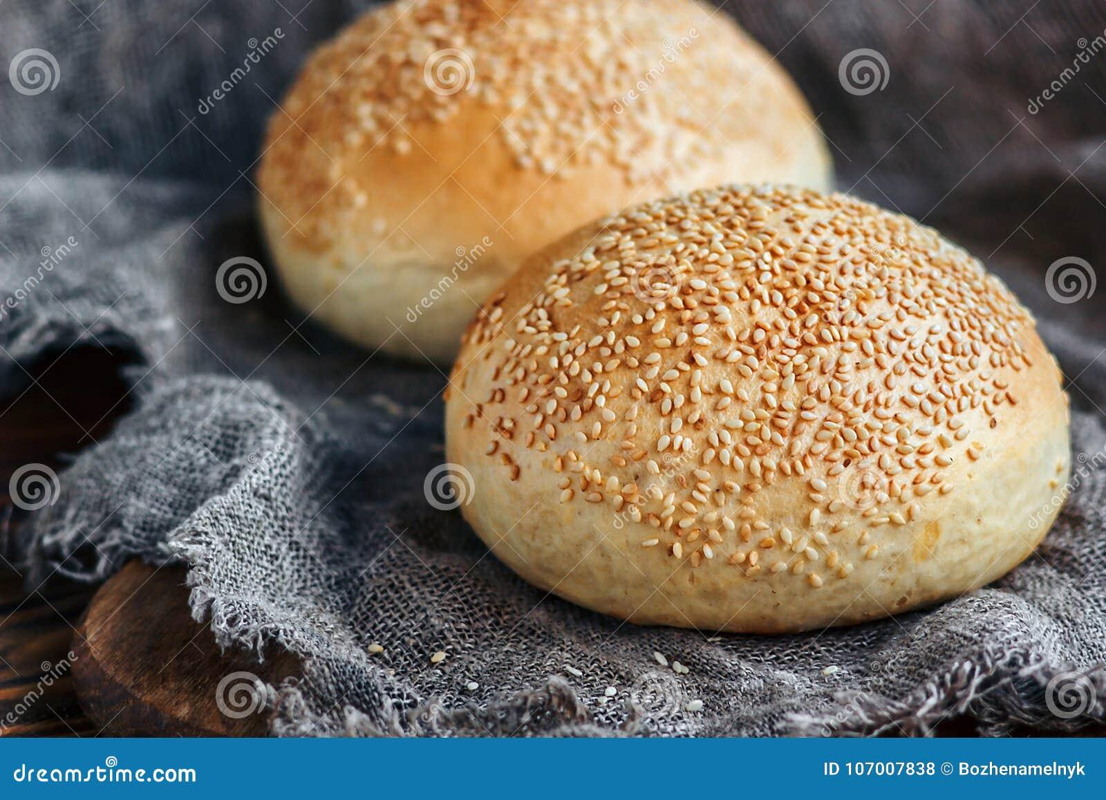 Round bun, sesame bun, bread rolls. Tasty burger bread with sesame on wooden, burlap background. Freshly baked hamburger buns. Top