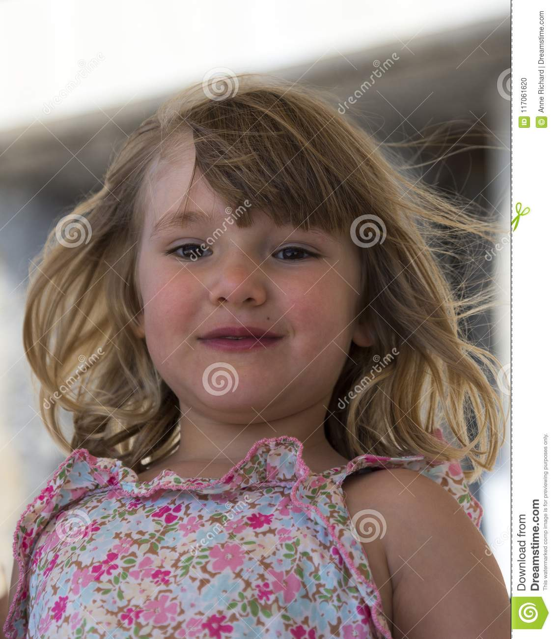Round Faced Adorable Little Girl With Very Wind Blown Dirty Blonde