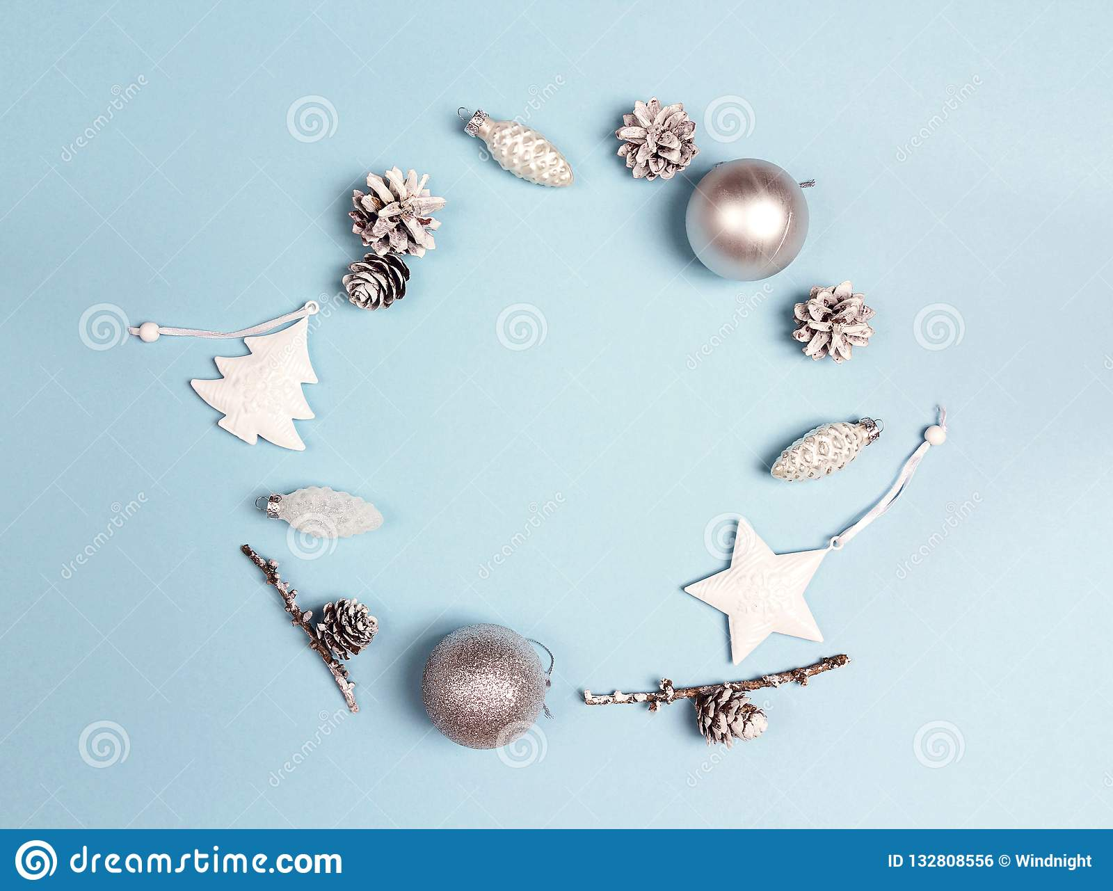 Round frame of Christmas decorations with copy space on blue background. Wreath composition of cones, balls,tree and star.