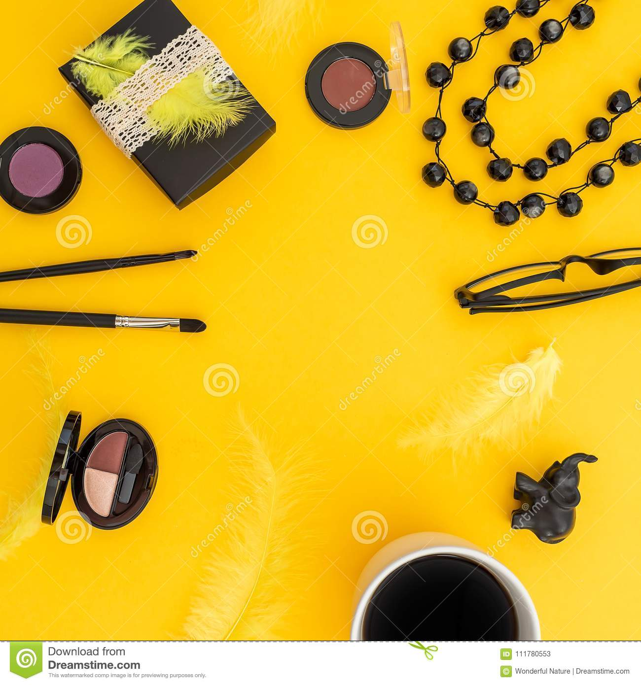 Round frame of gift box, glasses, cosmetics, bijouterie and accessories with mug of coffee on yellow background. Blogger concept w
