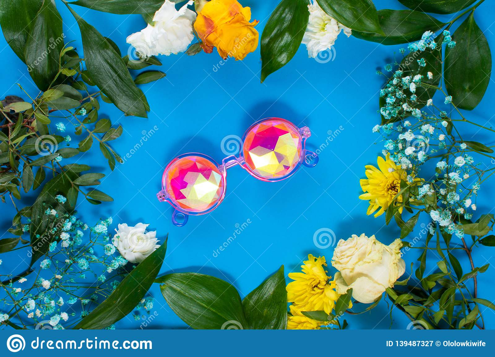 Round frame made of yellow and white summer flowers with green leaves.