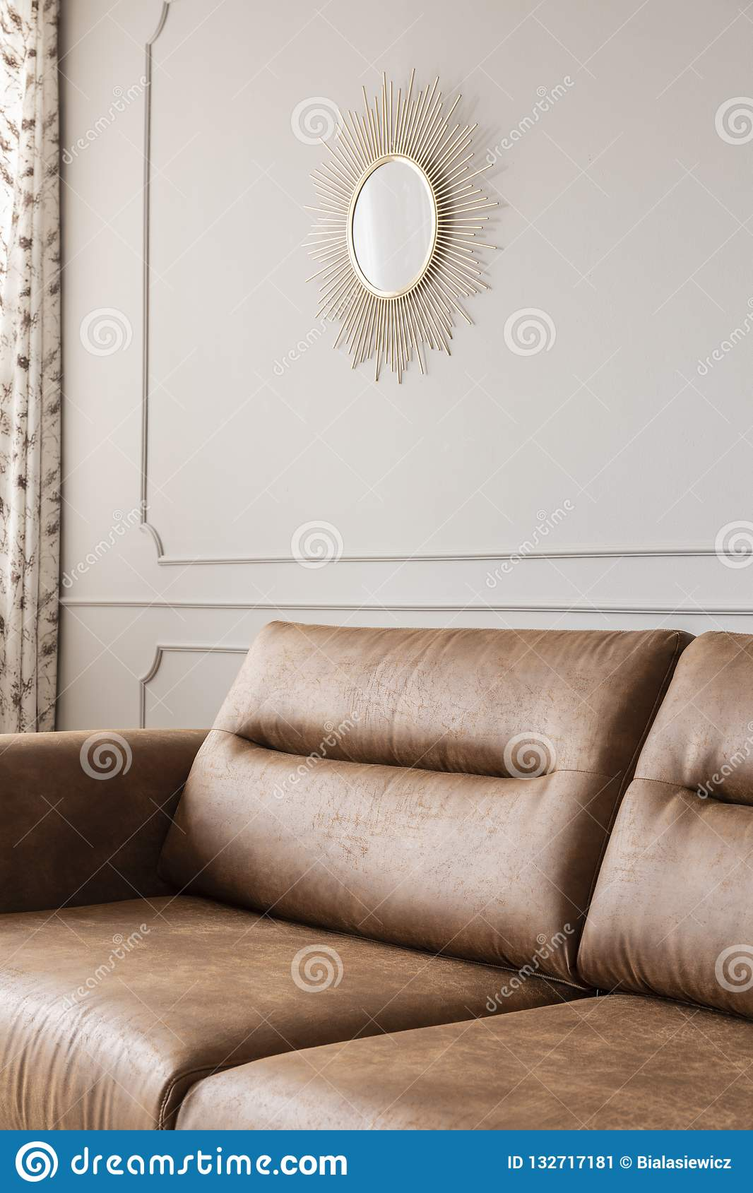 Round Gold Mirror On The Wall With Molding In Bright Sitting