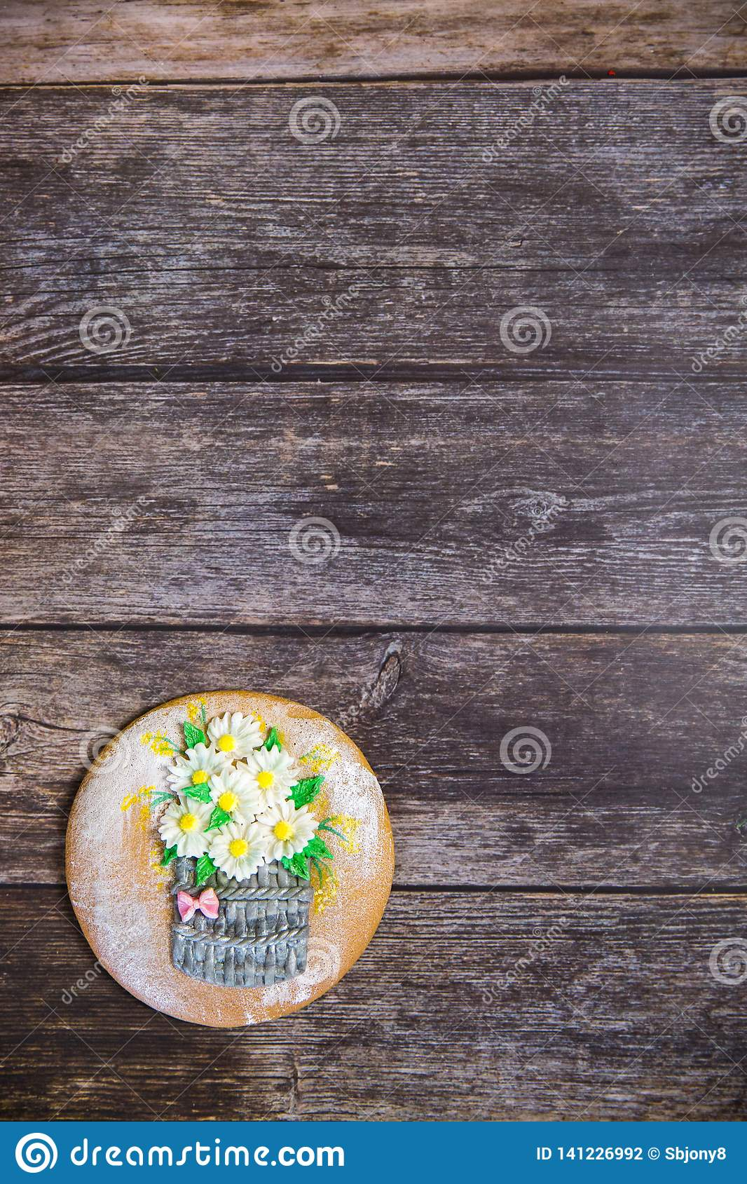 Round handpainted gingerbread on wooden background. Bouquet of daisies in a basket. Flat lay. Copy space. Sweet dessert as a gift