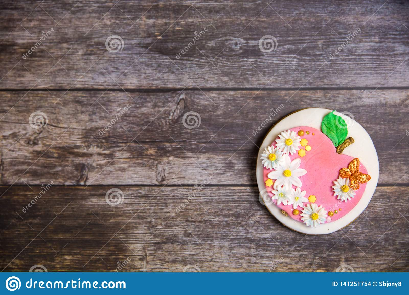 Round handpainted gingerbread on wooden background. Flat lay. Apple with flowers and butterflies. Copy space. Sweet dessert as a