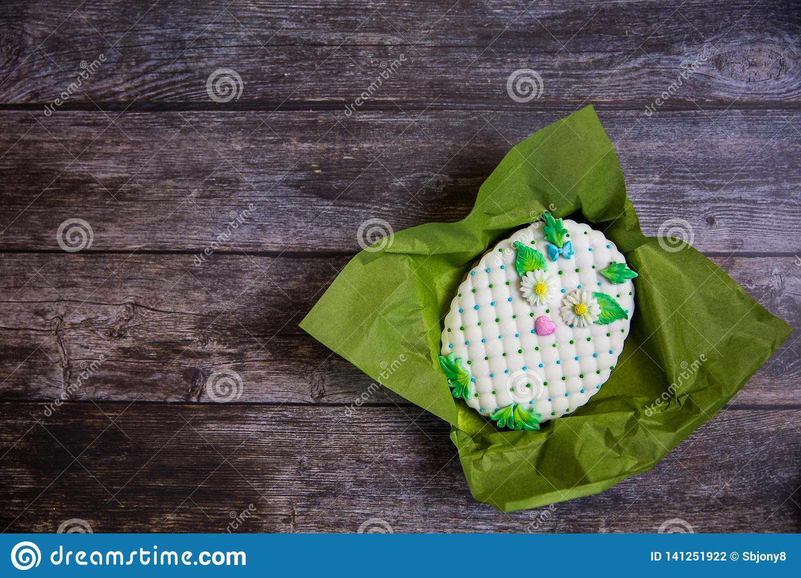 Round handpainted gingerbread on wooden background. White owl. Flat lay. Copy space. Sweet dessert as a gift for women`s