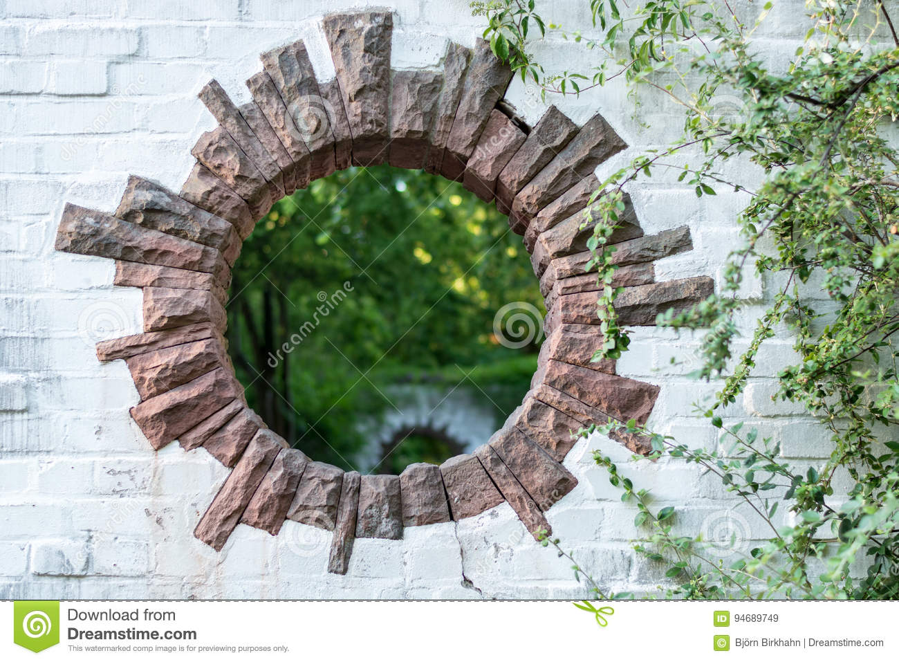 A round hole in a brick wall in a park looks like a portal