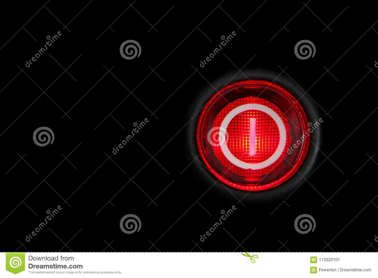 Round red power on and off button or switch with retro illumination glowing in the dark macro photography
