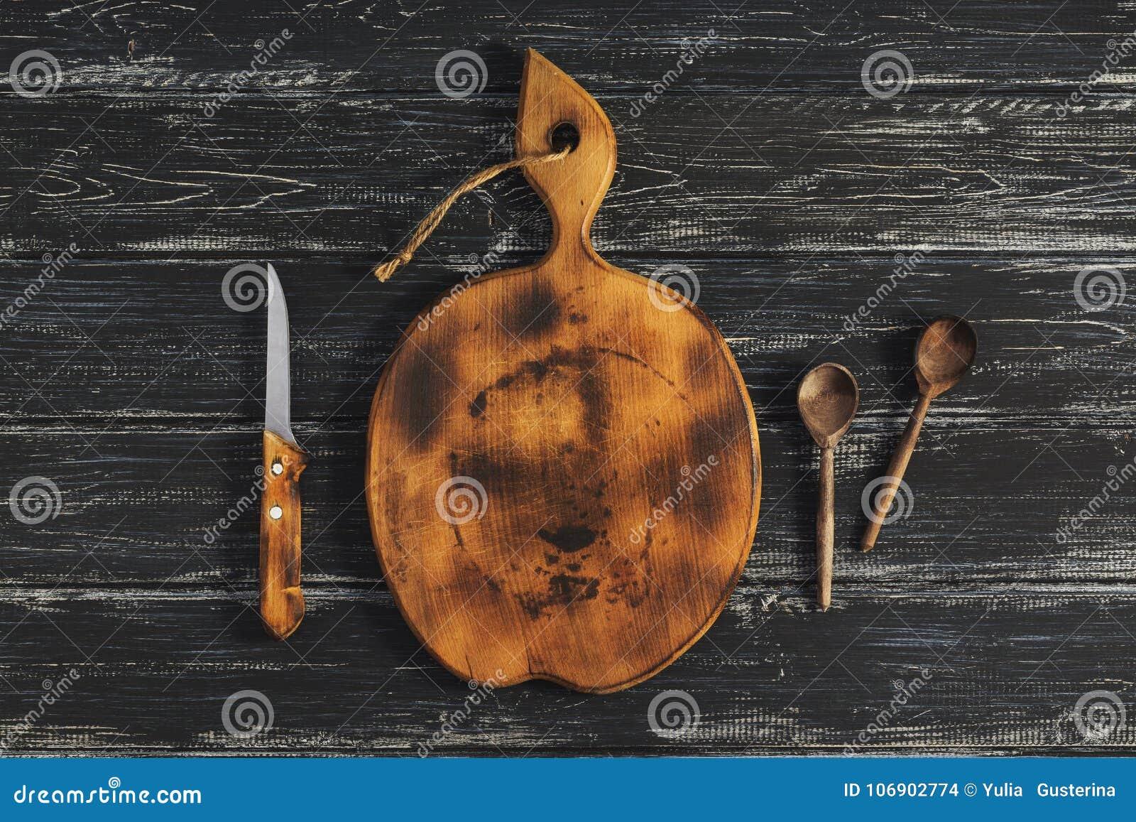 Round stara tnąca deska z drewnianą łyżką i nożem na ciemnym nieociosanym tle na widok