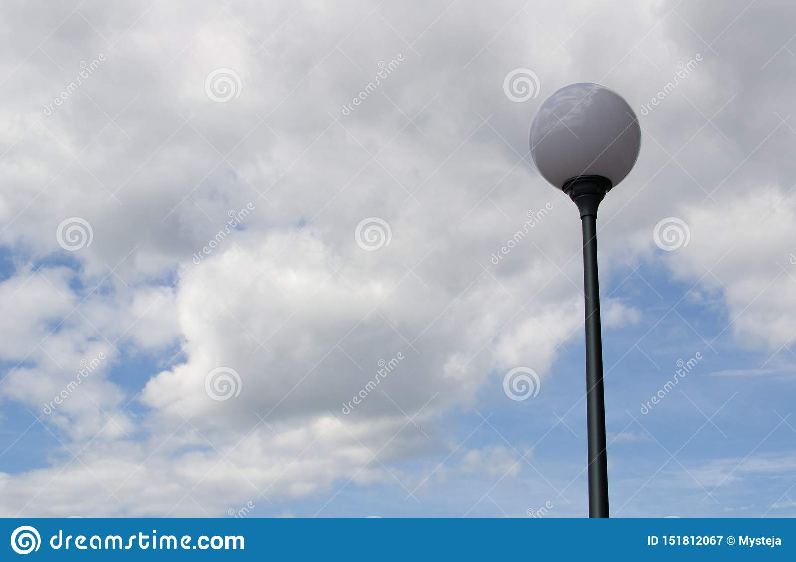 Round street lamp against a cloudy sky