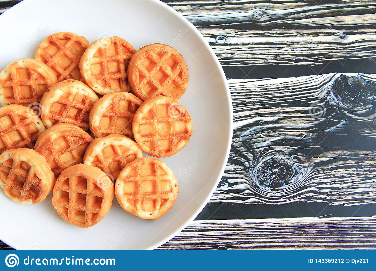Round waffles in a white plate on a brown wooden background