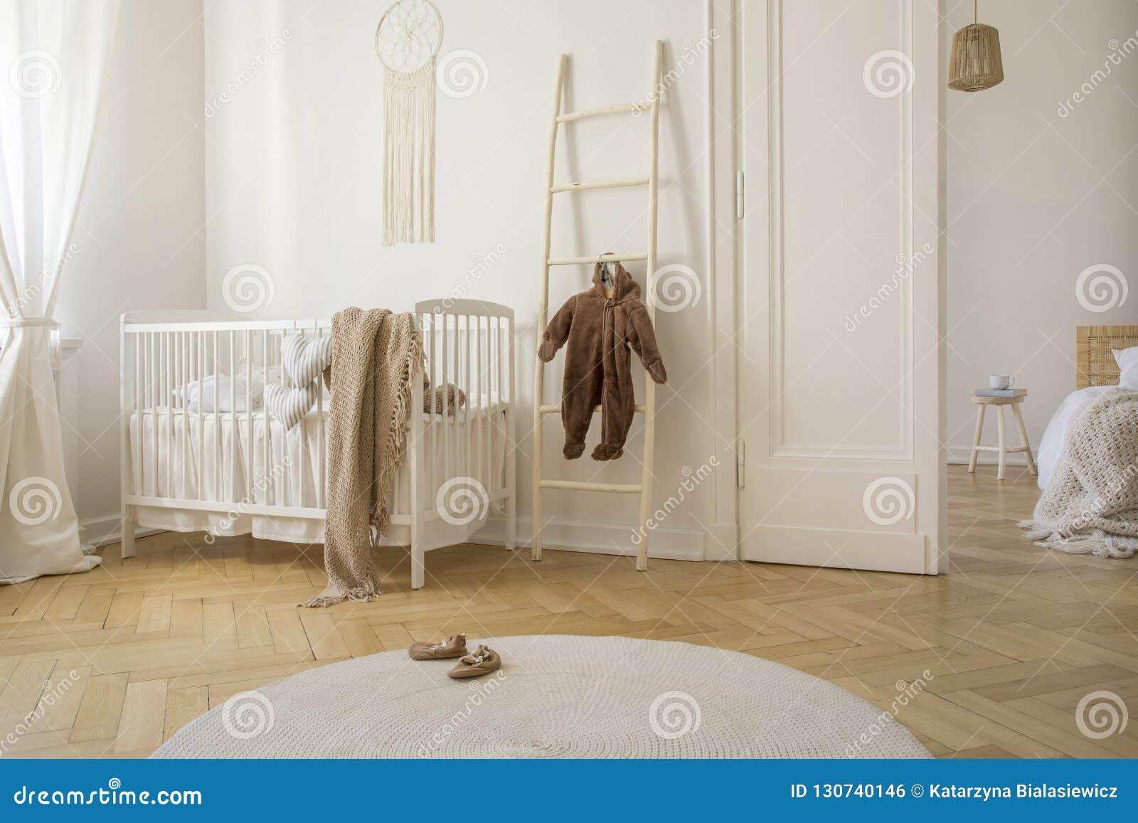 White carpet on the wooden floor of scandinavian nursery, real photo
