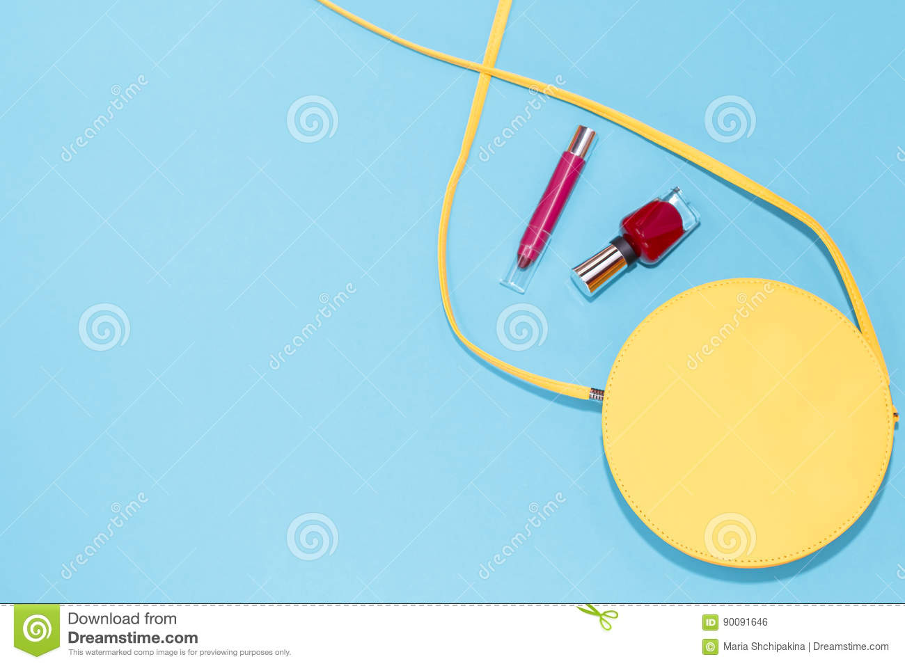Round yellow purse, red nail polish, red lipstick on a pastel blue background.