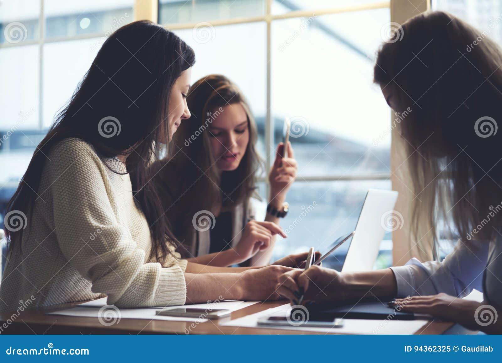 Roupa de desenhistas das meninas que trabalha junto no café usando laptop e na aplicação para a modelagem da Web usando o wifi