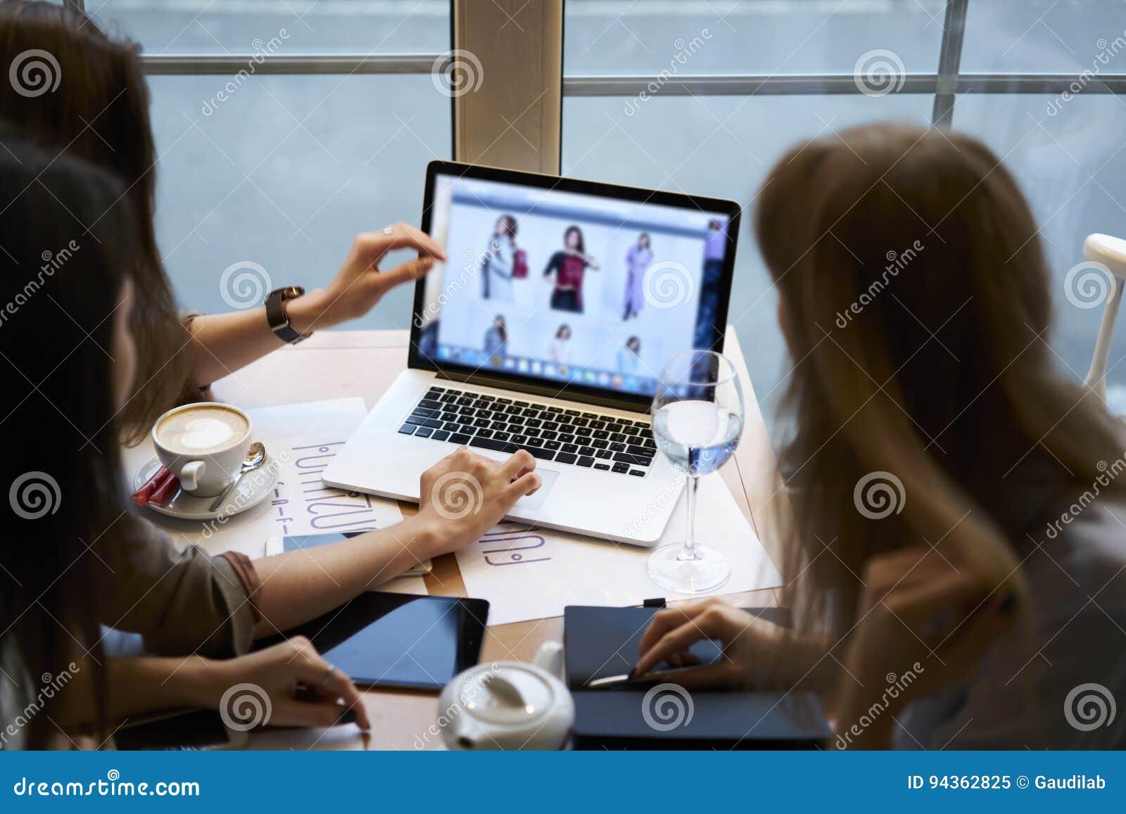 Roupa de desenhistas das meninas que trabalha junto o coffeebreak no café usando o laptop com zombaria acima da tela