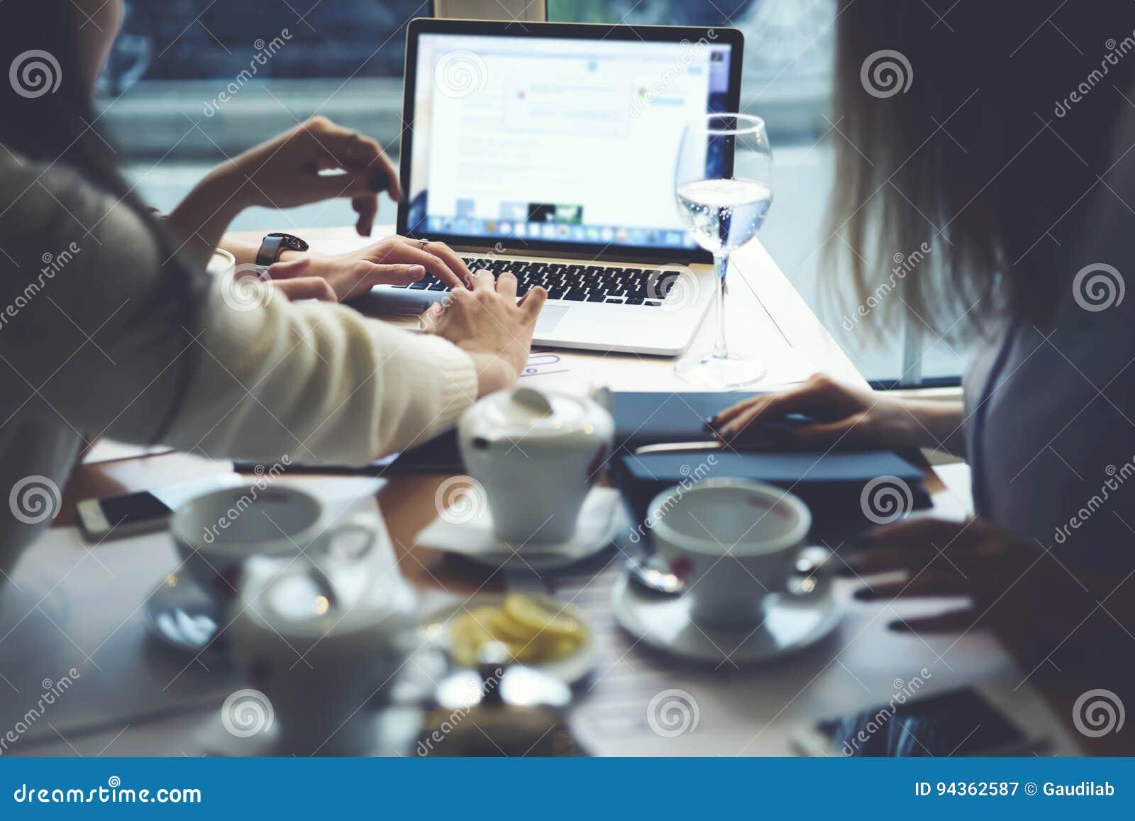 Roupa de desenhistas das meninas que trabalha o molde junto terminado do vídeo durante o tempo do chá usando o portátil com zomba