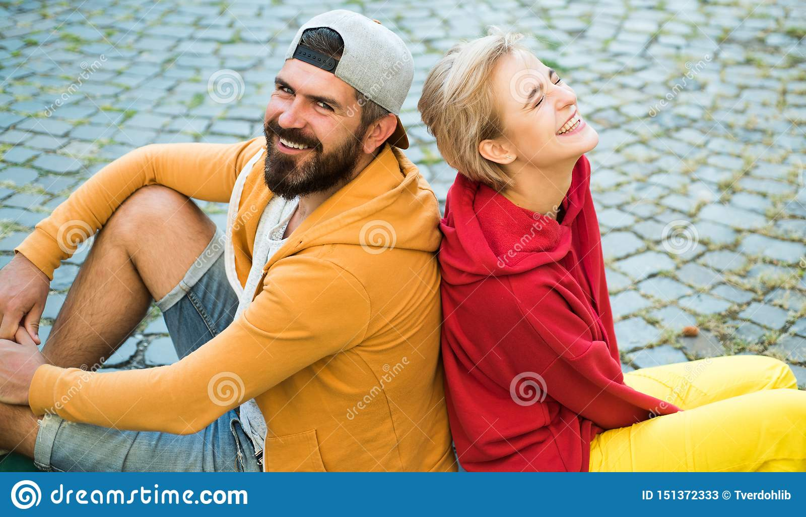 Roupa moderna do homem e da mulher para a juventude que relaxa fora Para sempre jovens Os pares penduram para fora junto Povos de