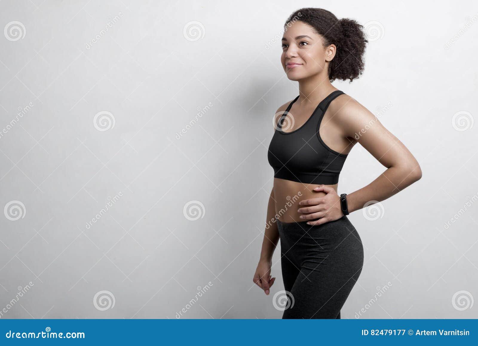 Roupa vestindo do exercício da mulher com perseguidor da aptidão