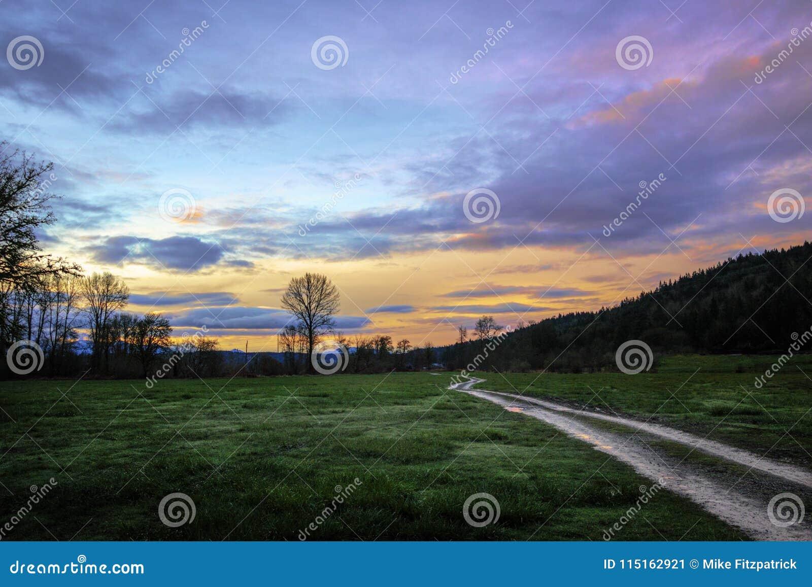 Route à deux rails de champ au lever de soleil