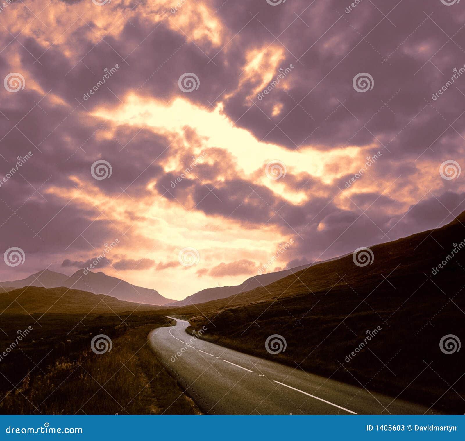 Route par le coucher du soleil de montagnes