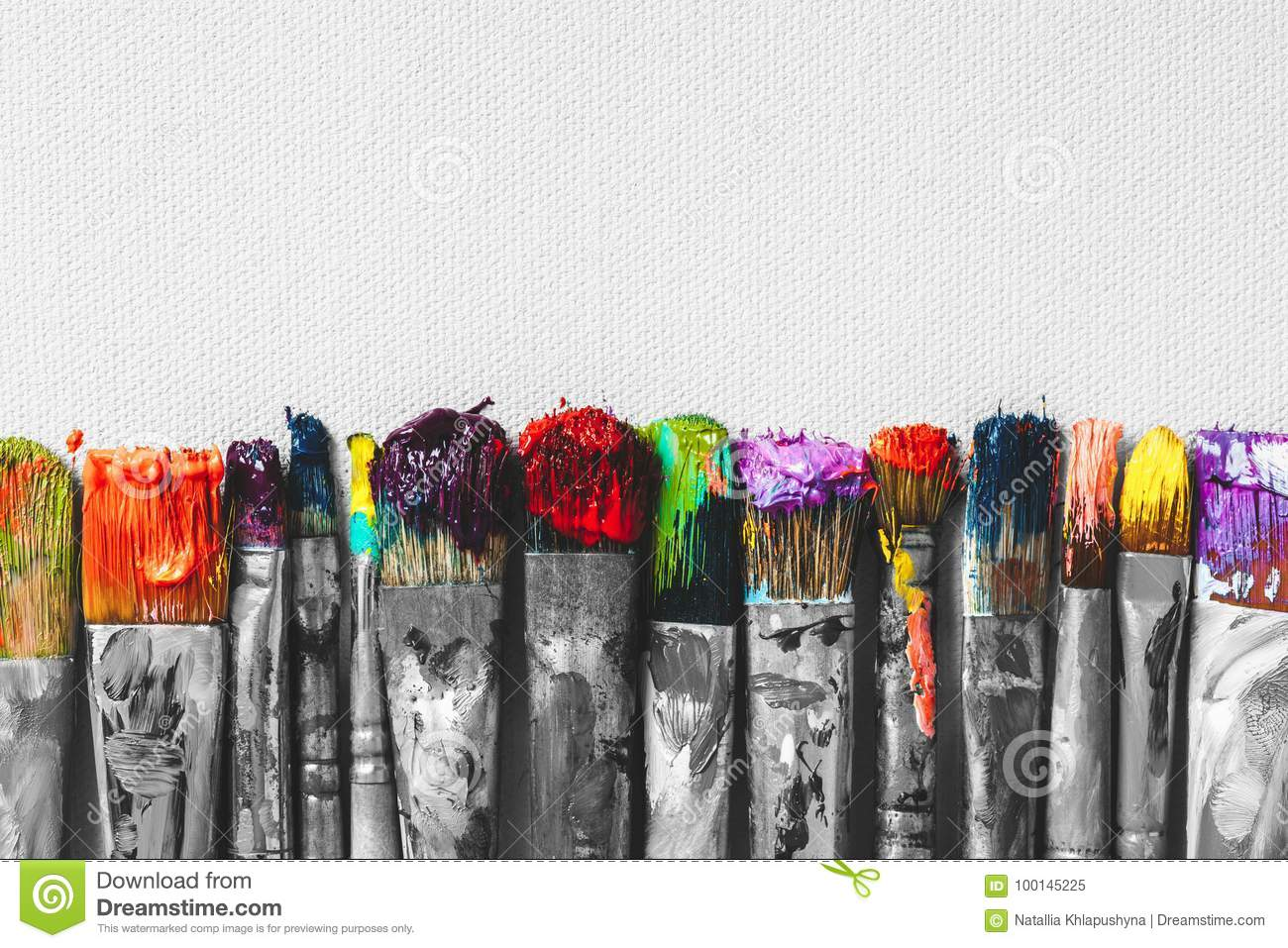 Row of artist paintbrushes with colorful bristle closeup